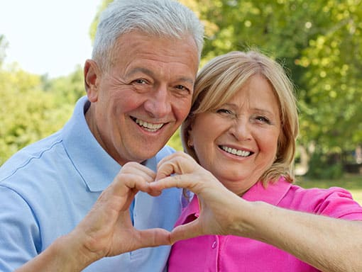Portrait of Elderly Couple Smiling and Forming a Heart with Their Fingers
