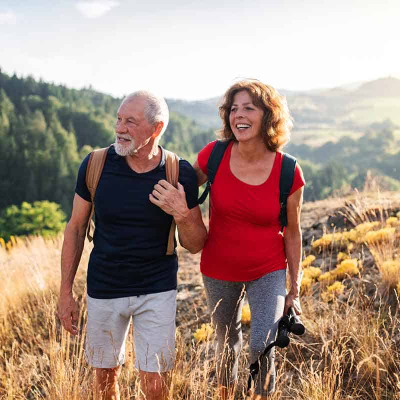 Portrait of Elderly Couple Hiking Mountains and Smiling