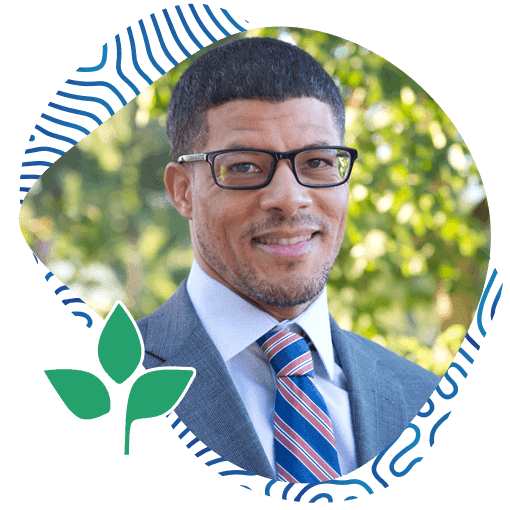 Portrait of Afro-American Man Wearing a Suit with a Tie and Glasses with a Natural Background. Ayo