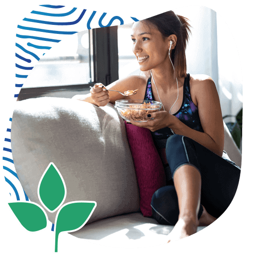 Portrait of Young Fitness Asian Lady Eating Cereals and Listening to Music on Earphones