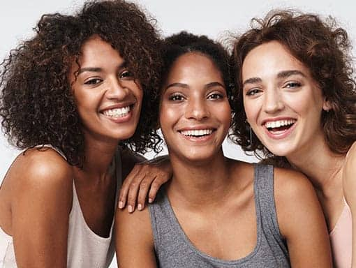 Portrait of Three Young Smiling Girls Looking at the Camera Reflecting Beautiful Skin